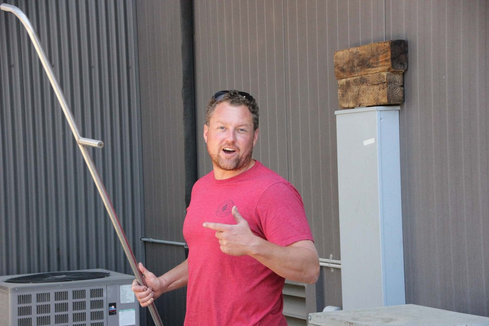 Ryan in the winery carrying a punchdown tool
